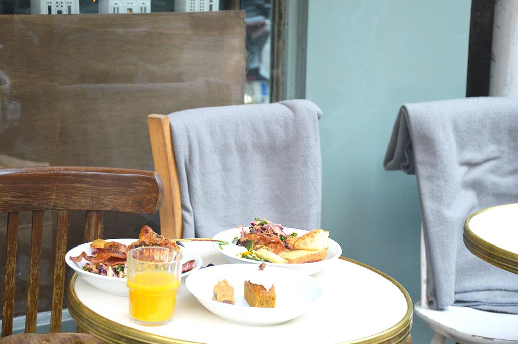 Terrasse de La Bossue avec des plats sur la table, une des adresses gourmandes à Montmartre